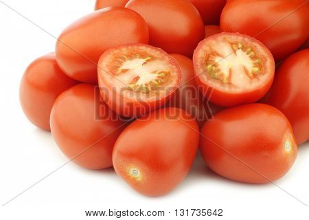 fresh and colorful italian roma tomatoes and a cut one on a white background