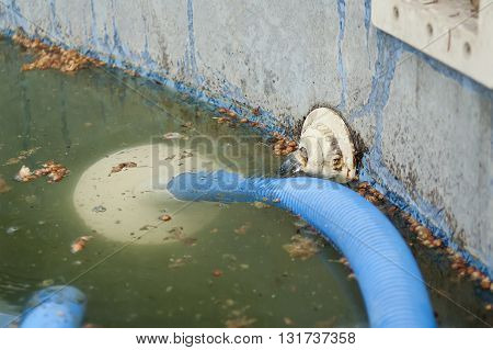 Dirty water and plastic pump hose in an abandoned waterpool selective focus outdoor shot