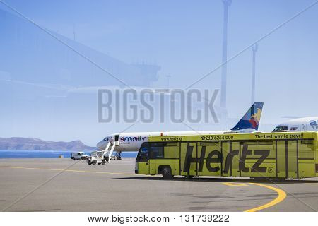 HERAKLION GREECE - APRIL 28 2016: Aircraft Airbus A320 Polish airlines Small Planet is on pre-flight preparation at Heraklion Airport N. Kazantzakis. In foreground is yellow bus Cobus 3000. In reflection on glass is visible the profile of airport building