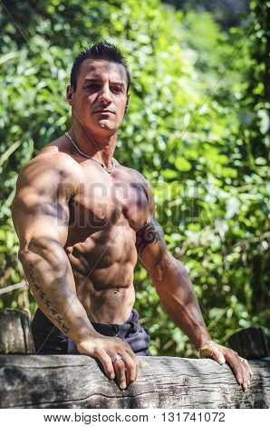 Attractive shirtless young muscleman outdoors in nature. Green environment all around him