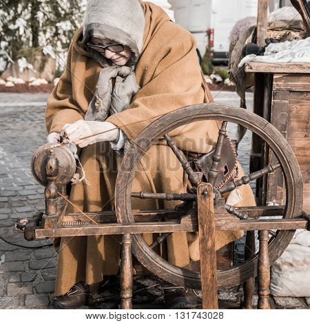 Trento, Italy - January 8, 2016: Elderly woman uses the cocoons of silkworms to spin using an old spinning wheel of wood.
