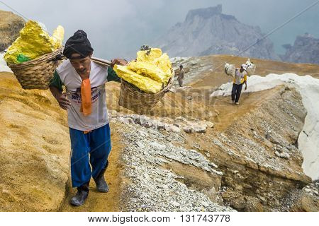 Kawah Ijen Crater, East Java, Indonesia - May 25, 2013: Sulfur miner carrying sulfur-laden baskets at Kawah Ijen volcano in East Java, Indonesia.
