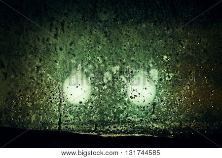 Dim lights outside night window in inclement weather