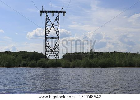 metal pillar stands on the banks of a large river. The mountain and forest, long wires