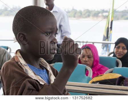 ZANZIBAR TANZANIA - JUNE 16: boy on the ferry that connects Zanzibar island to the mainland on June 16 2013 in Zanzibar