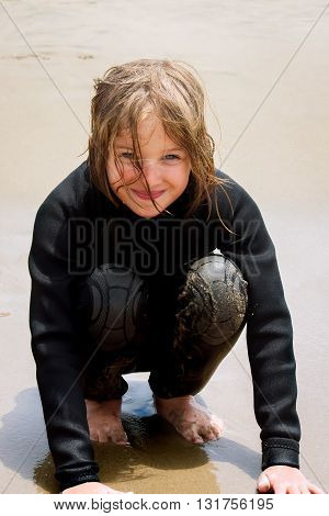 A young girl crouches in wet beach sand. She is wearing a wet suit and is wet and sandy but very happy. She has a smirky smile and imprints from goggles that she had been wearing earlier around her eyes.