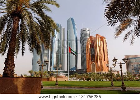 ABU DHABI CORNICHE, 30 MARCH 2016. Editorial Photograph of Emirates Flag in front of High Rise Buildings including the 5 Towers of Etihad Towers, the Regent Emirates Pearl and the recently completed Millennium Bab Al Qasr Hotel
