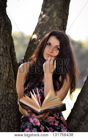 Beautiful, attractive, pretty, lovely, cute, perfect, gorgeous, adorable girl with a book. Amazing girl sitting in the green park, near the trees with beautiful girl. Brunette girl read really interesting book.