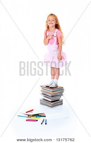 Portrait of a little girl standing on a stack of books. Isolated over white background.