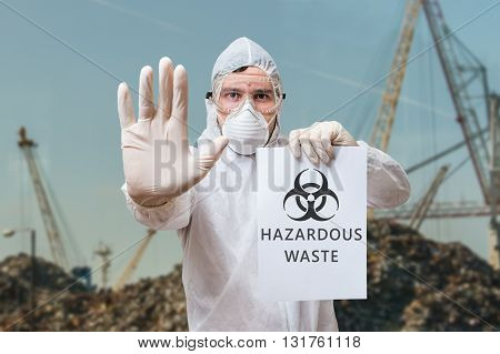 Technician In Coverall Warns In Landfill About Hazardous Waste.