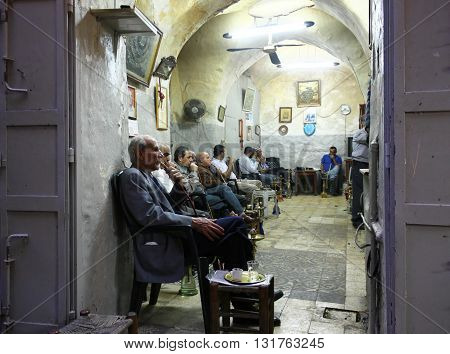 JERUSALEM OLD CITY MARKET, ISRAEL, 1 APRIL 2013 - Editorial Photograph of Men Smoking In The Old City Market. Smoking is a much enjoyed part of the social culture in many parts of Asia, though studies have highlighted health risks due to toxic and carcino