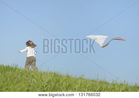 Girl child playing kite flying enjoying carefree childhood