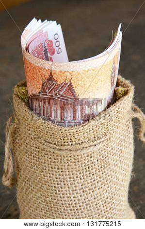 Cambodia riel notes in a brown hessian bag.