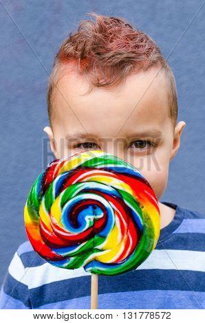 Boy with an Orange Mohawk Eats a Lollipop / A young boy with an orange mohawk eats a large lollipop