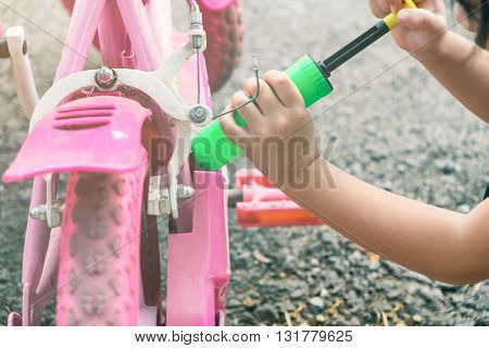 Selective focus on kid's hand acting like using air pumping inflate her bicycle tire - kid's play kid's imagination