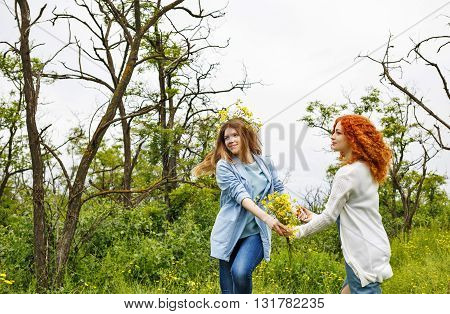 Best friends forever. Friends holding hands. BFF. A girl holding a bouquet of wildflowers. A wreath of flowers on the head of the girl.