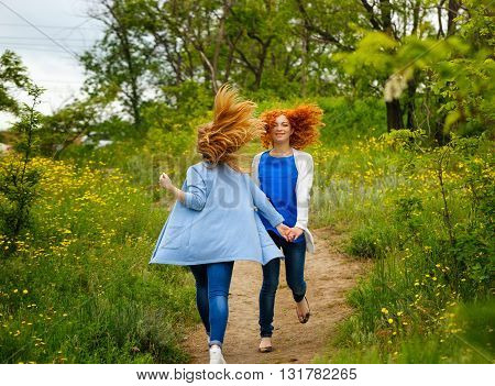 Best friends forever. Girlfriends walking hand in hand in the park. BFF. Close friends. Gentle friendship.