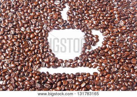 White coffee cup in many brown coffee beans for background