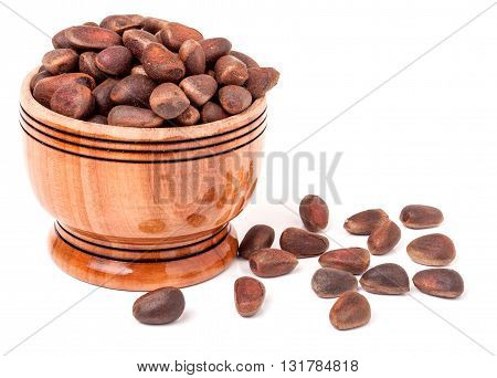 unpeeled cedar nuts in a wooden barrel on a white background