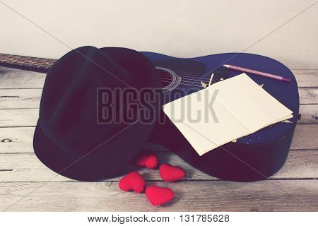 Vintage tone:guitar Heart hat Book Pencil on wood table