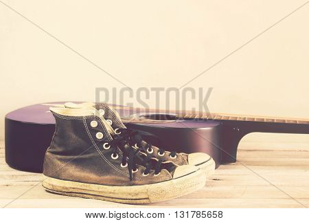 Vintage tone:guitarsneakers on wood table for use as Background