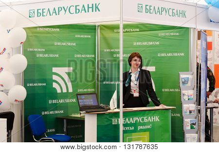 GOMEL BELARUS - MAY 19 2016: Unknown young woman (bank employee) stands near demonstration stand of JSC