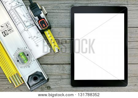 Construction Tools With Blueprint And Digital Tablet Over Gray Wooden Background
