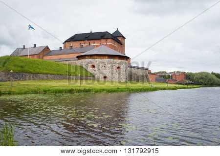 HAMEENLINNA, FINLAND - JUNE 21, 2014: A view of the ancient fortress-jail Hameenlinna by Vanajavesi lake. Historical landmark of the Finland