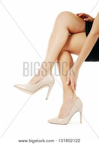 Female legs in beige high-heeled shoes on white background