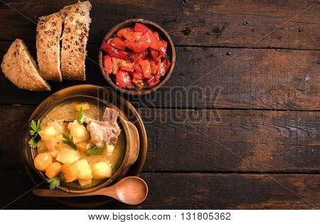 Stew soup and pepper salad on rustic background