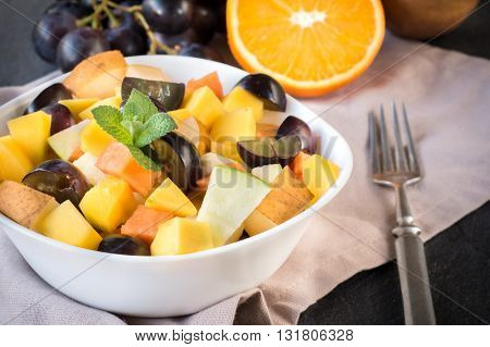 Photos of tropical fruit salad on rustic background