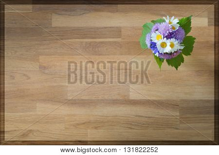 top view of wooden background with flowers in corner for greeting card