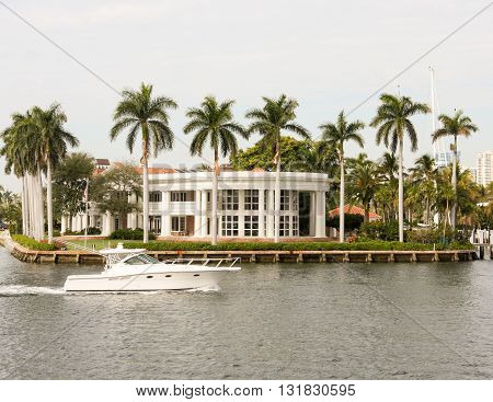 White speedboat in front of waterside mansion in Miami Florida