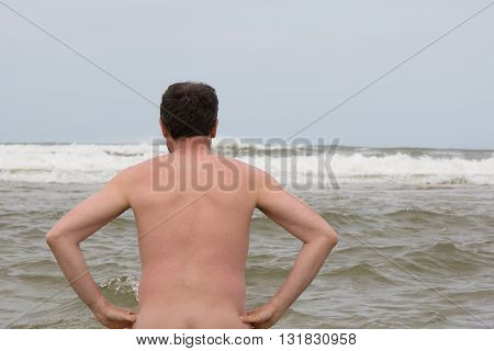 Man Naturist In The Water Under Deep Blue Sky