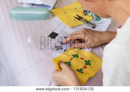 Closeup On Person Embroidering Cross Stitch With Needle And Thread
