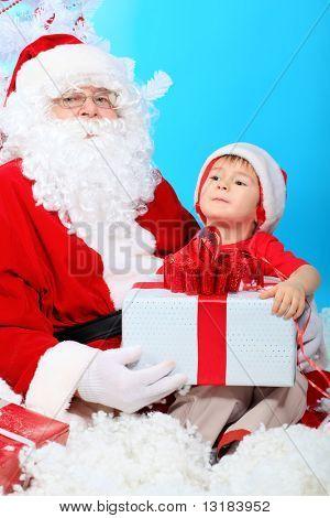 Thema Weihnachten: Weihnachtsmann und kleiner Junge mit Geschenken.