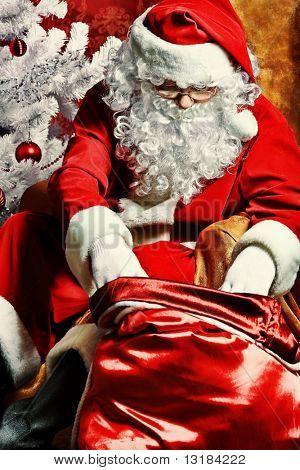 Santa Claus mit Geschenken und Neujahr Baum zu Hause. Weihnachten.