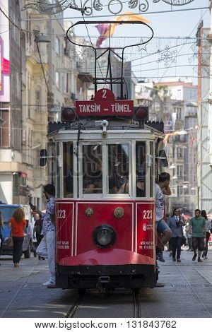 ISTANBUL TURKEY - JULY 08 2015 : The Taksim Tunel Nostalgia Tram trundles along the istiklal street and people at istiklal avenue