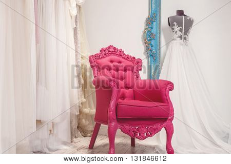 Fashionable pink chair near wedding dresses in salon