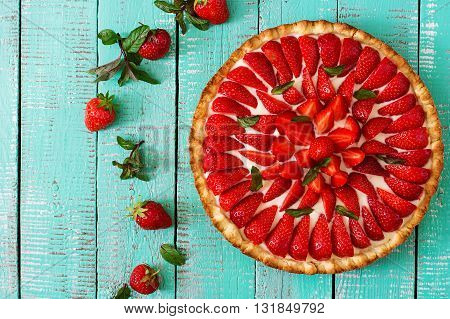 Tart With Strawberries And Whipped Cream Decorated With Mint Leaves. Top View