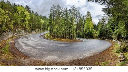 Curved serpentine mountain road in romanian carpathian. Panoramic montage from 3 HDR images