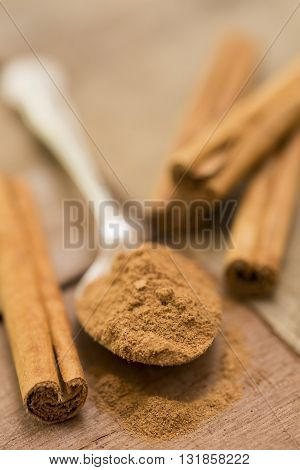 Ground Cinammon And Sticks With Spoon On Wood