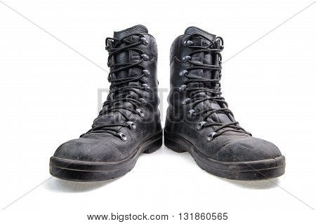 Old used dirty army leather boots with untied laces on a white background