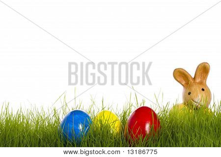small easter bunny with easter eggs in grass