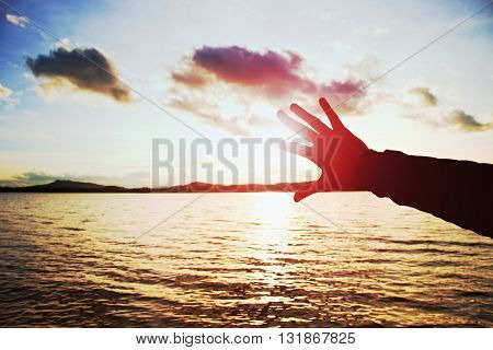 Silhouette Of Hand And Lomg Fingers Try To Touch The Sun,  Sunset Above Ocean . Vivid Colors.
