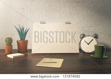 Closeup of office table with blank card plants coffee cup alarm clock and stationery items on white brick background. Mock up 3D Rendering