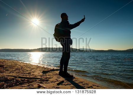 Man Holding Cellphone, Taking Picture Of Autumn Sunset Or Sunrise In Picturesque Sea Scenery