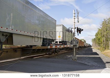 Truck trailers being transported on flat train cars pass a railroad crossing safety barrier.