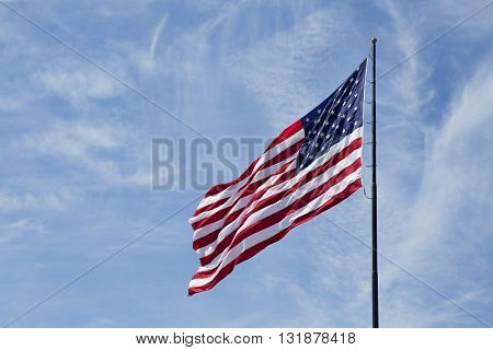 American Flag flutters in the breeze of a crisp clear Spring day. Old Glory is shot against a light blue sky with a few wispy clouds.