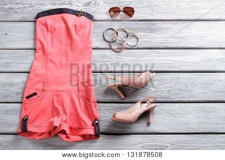 Jumpsuit shorts and heel shoes. Salmon jumpsuit shorts. Attractive outfit with sunglasses.